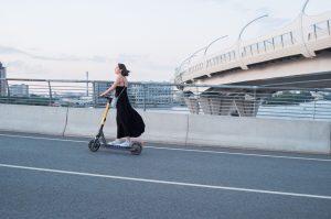 A photo of a woman riding an E-scooter.